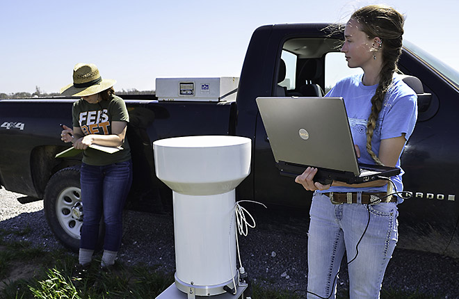Two technicians collect data from a rain gauge