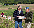 Scientists collect runoff samples and review plot layouts in a field