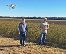 Scientists flying drone to search for weeds in a field
