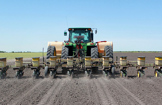 Tractor plants cotton and applies fungicide to field
