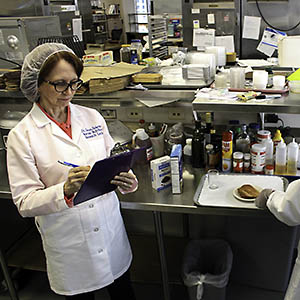 Two people prepare food for study participants
