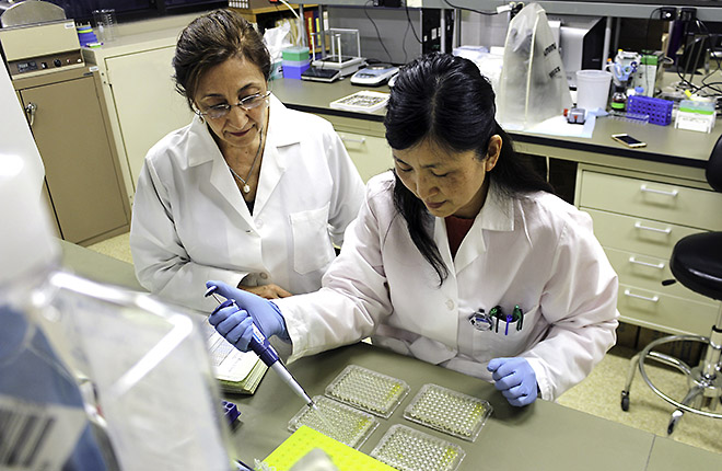 Two researchers preparing samples in the lab