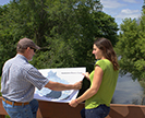 Two scientists reviewing a map in front of Beaver Creek.
