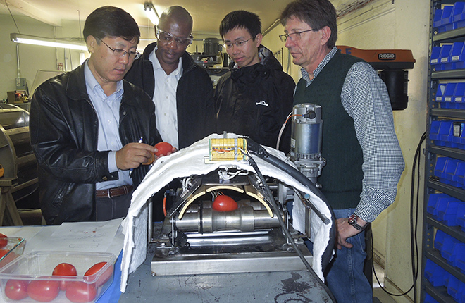 Researchers test prototype infrared peeling equipment.