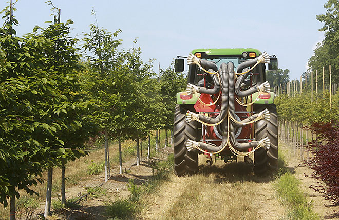 Tractor with new variable sprayer applying pesticides at a nursery.