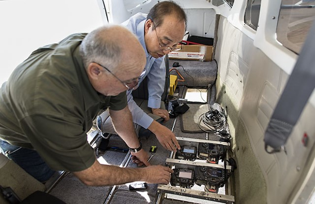 Scientists installing camera equipment inside airplane