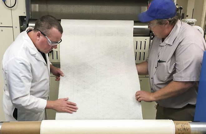 Two ARS employees inspect cotton nonwoven fabric