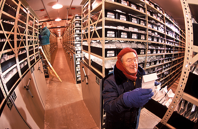 Two scientists retrieve seeds from a cold-storage vault