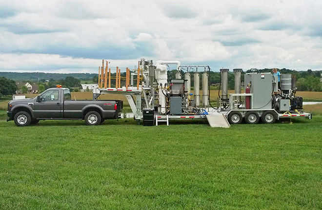Mobile pyrolysis system on a farm field.