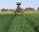 Tractor applying fertilizer to a field