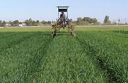Tractor applying fertilizer to a field