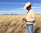 Scientist with smartphone on rangeland
